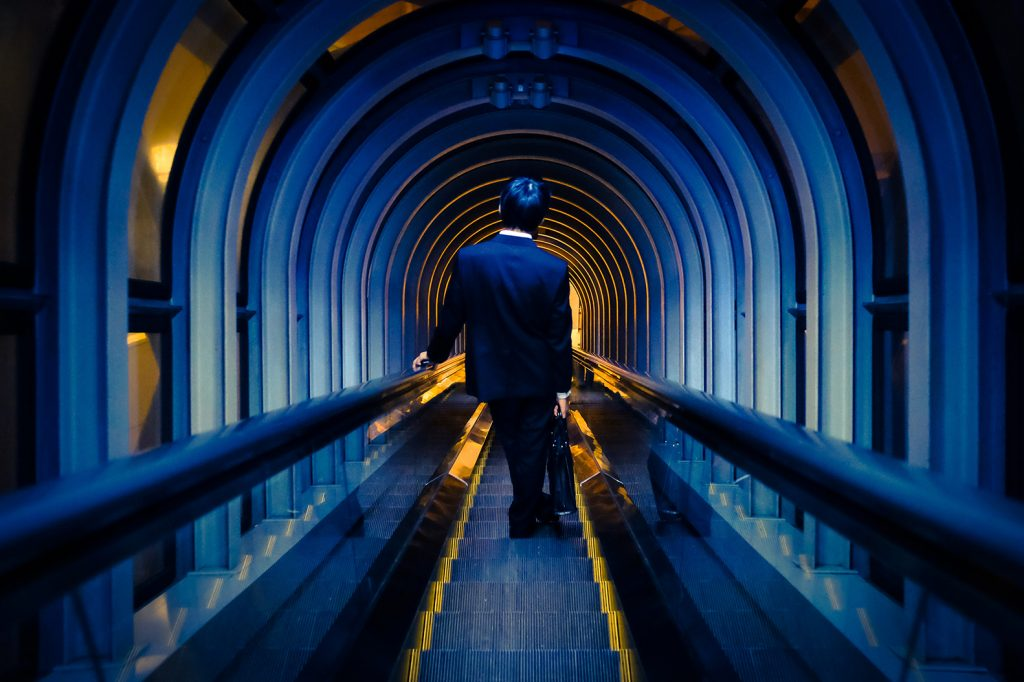 Man walking down escalator after work